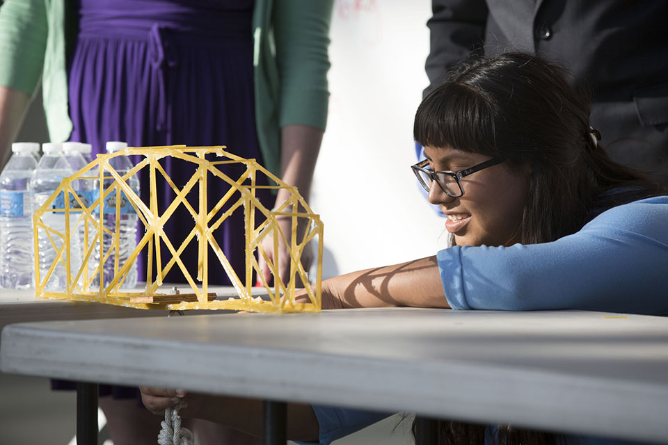 Aspiring engineers in CSUCI's Summer Bridge program to test the strength of their spaghetti bridges